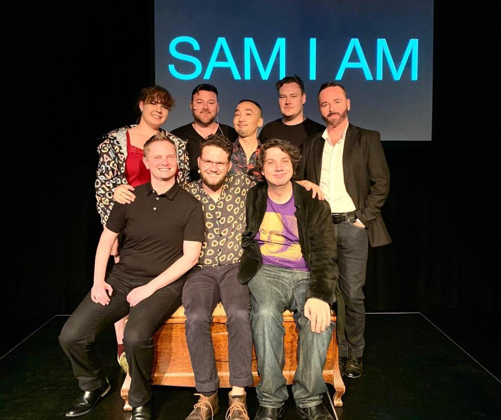 A group of actors sitting on a box in a black theatre with a screen behind them with the words Sam I am.