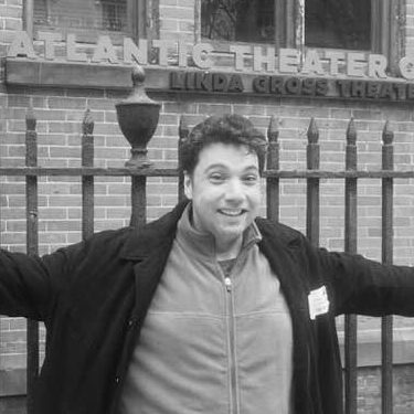 A man with outstretched arms in front of a theatre with the words Atlantic Theatre visible.