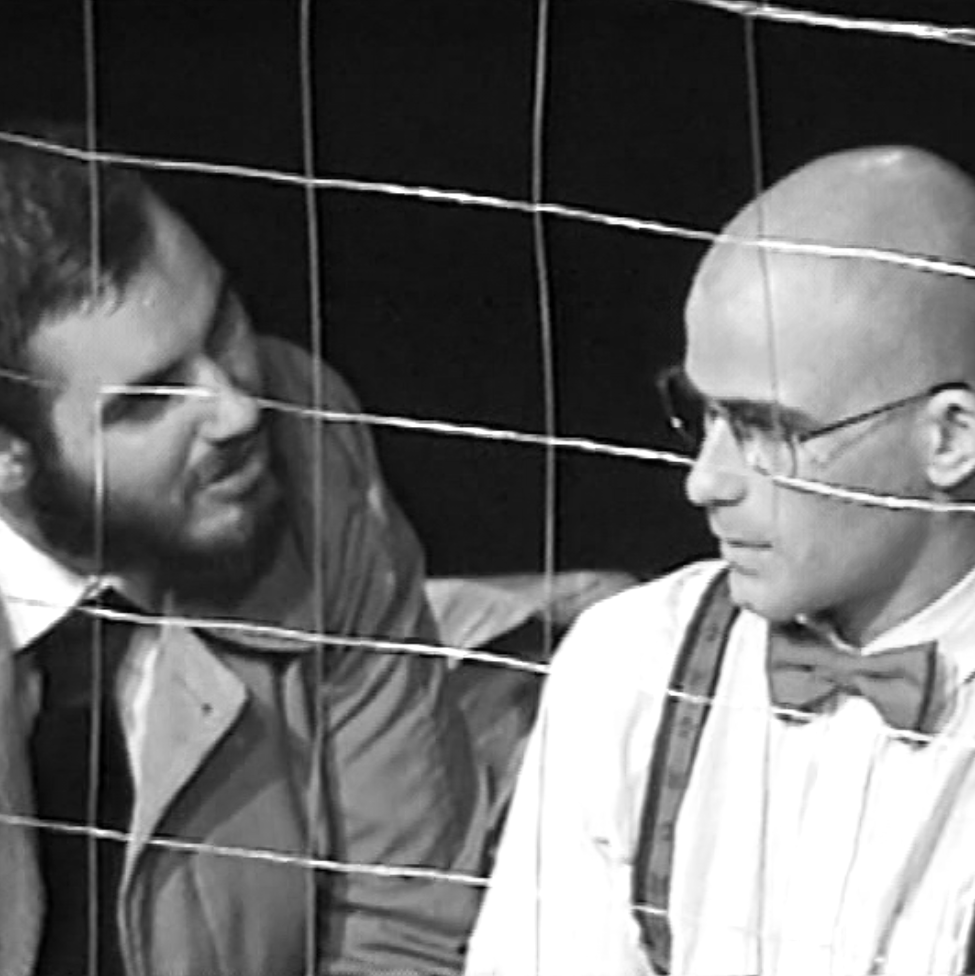 Two men in conversation behind barbed wire. The image is in black and white.