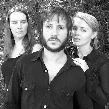 A black and white image of three actors, a man with a coloured shirt and two female actresses on the side of the male actor.