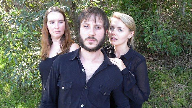 Three actors in an outdoor setting. All actors are wearing back clothes. One male and two females