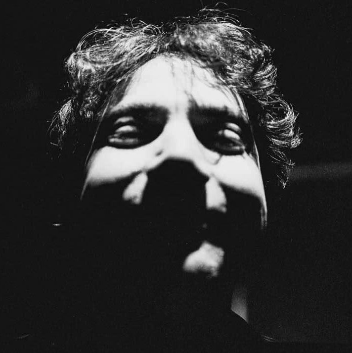 An image of a man's face in shadows.