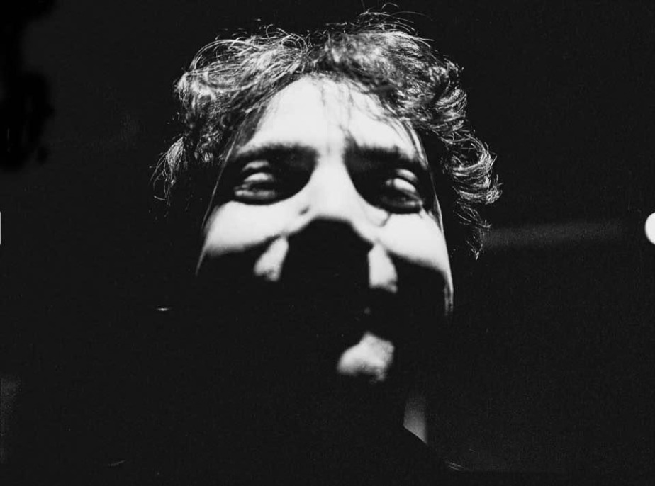 A headshot of a man in black in white with lots of shadows