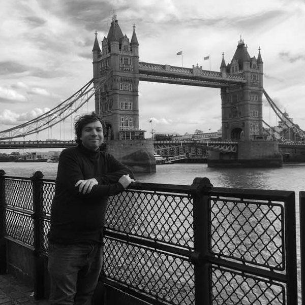 A man posing in front of a bridge. The bridge is Tower Bridge in London, UK.